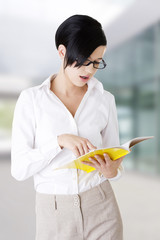 Young focused female reading book