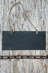 Chalkboard with metal chain on the old wood