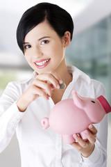 Businesswoman putting a coin into piggy bank