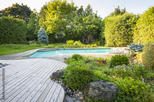 Leinwanddruck Bild Garden and swimming pool in backyard