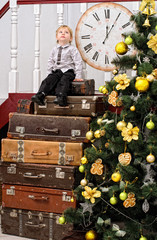 boy on pile of suitcases at christmas tree