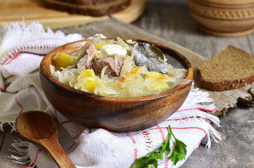 Rustic sour cabbage soup with goose in a wooden bowl.