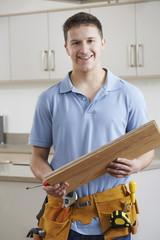 Portrait Of Carpenter Installing Fitted Kitchen