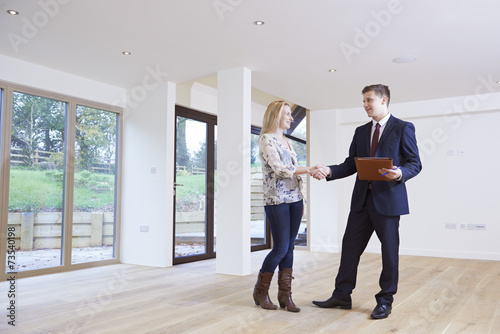 Woman Shaking Hands With Estate Agent In New Home - 73540198