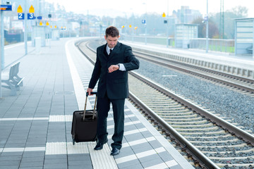 man in suit on business trip is looking on his watch