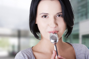 Young smiling woman with spoon
