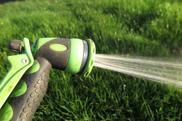 Watering fresh green lawn grass with an adjustable shower