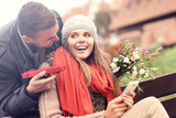 Fototapety Man giving surprise gift to woman in the park