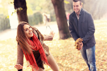 Happy couple having fun in the park in autumn