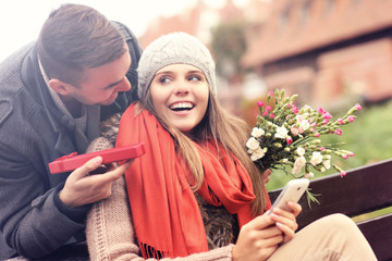 Man giving surprise gift to woman in the park