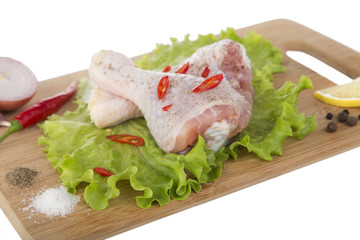 Raw chicken legs on wooden blackboard with lemon
