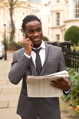 business man holding a newspaper and talking on the phone.