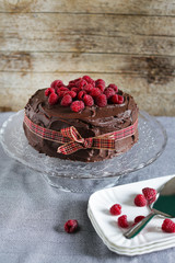 Raspberry chocolate cake with fresh berries tied with ribbon