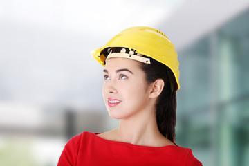 Female worker in helmet looking up.