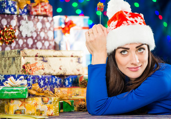 pretty brunet in holiday hat at colorful gifts background