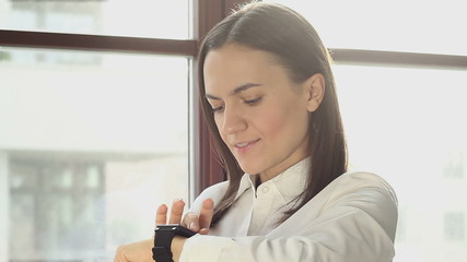 Smiling businesswoman using a smart watch in the office