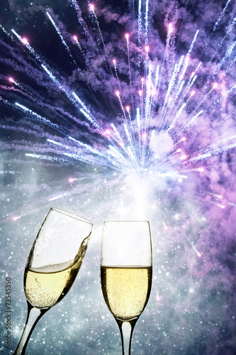 Champagne glasses against holiday lights and fireworks - 73545350