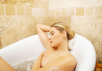 Relaxing woman propping up on bath by elbow