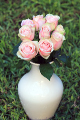 Pink roses in a vase against a grass
