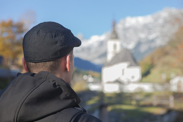 Man from behind is looking on a church