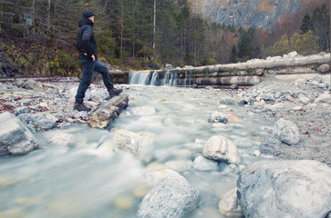 Man standing in the  wild on a brook waching a waterfall