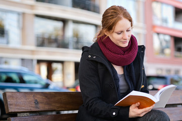 Woman Reading a Book in a City