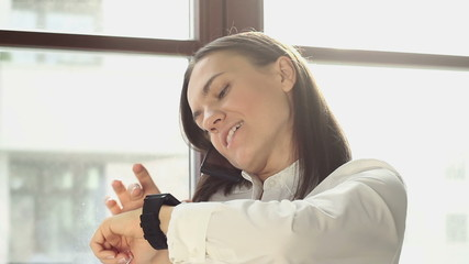 Woman with mobile phone and smart watch in the office