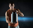 young male bodybuilder holding jar with protein