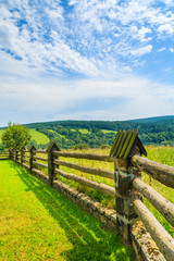 Wooden fence on green field in Bieszczady Mountains, Poland