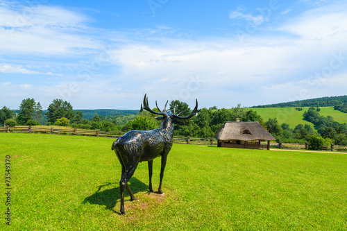 Deer statue on green field in Bieszczady Mountains, Poland
