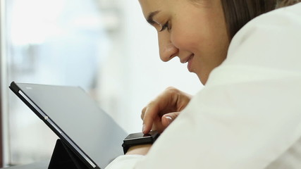 Happy woman using tablet computer and smart watch in the office