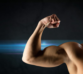 close up of young man flexing and showing biceps