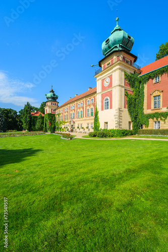 Green gardens of Lancut castle on sunny summer day, Poland - 73549597