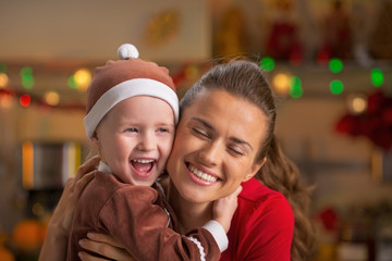Portrait of happy mother and baby hugging in christmas kitchen