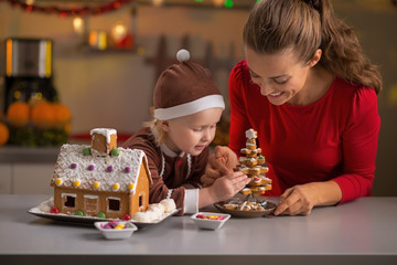 Happy mother and baby making christmas cookie house