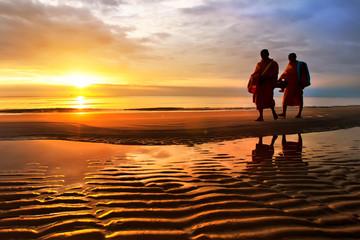 Silhouettes of monks on Hua Hin beach Thailand