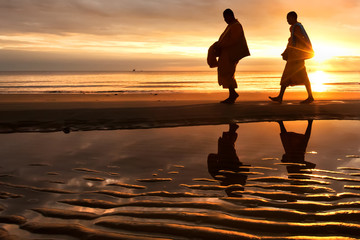Silhouettes of monks on Hua Hin beach Thailand