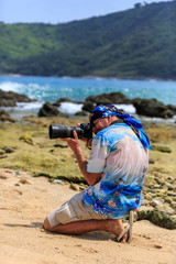 Male photographer with DSLR camera on the beach