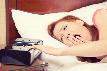woman extending hand to alarm clock yawning lies in bed