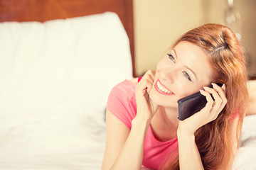 happy young smiling woman using mobile phone lying in bed