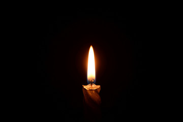 Silver candle burning on a black background