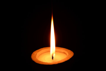 White candle burning on a black background