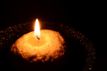 White candle on a plate burning on a black background