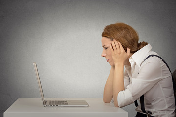 stressed young unhappy business woman working on laptop