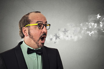 man with open mouth blowing cold breeze snowflakes flying away