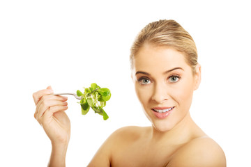 Nude woman eating lettuce