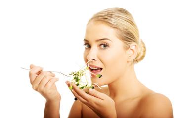Healthy nude woman eating cuckooflower