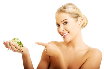 Healthy nude woman pointing on a cuckooflower