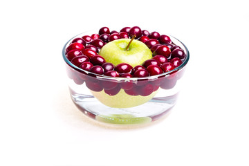 Cranberries and apple, small bowl, side view.