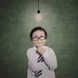 Business boy thinking gesture under lit bulb